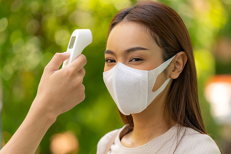 taking temperature of woman wearing face mask